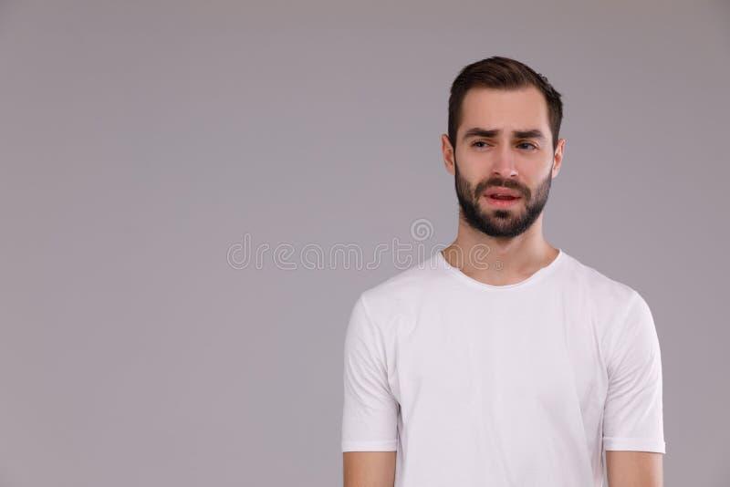 Stående av en man i en vit T-tröja på en grå bakgrund royaltyfri fotografi