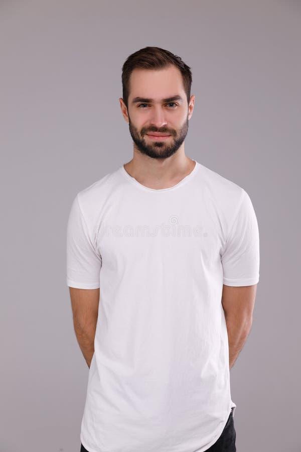 Stående av en man i en vit T-tröja på en grå bakgrund arkivfoton