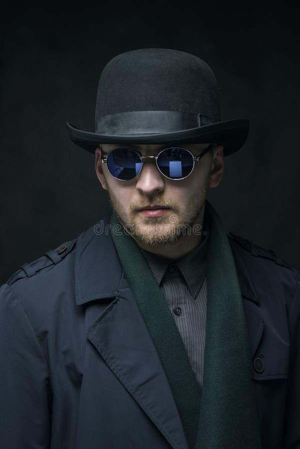 Stående av en man med ett skägg i en hatt och exponeringsglas arkivfoton
