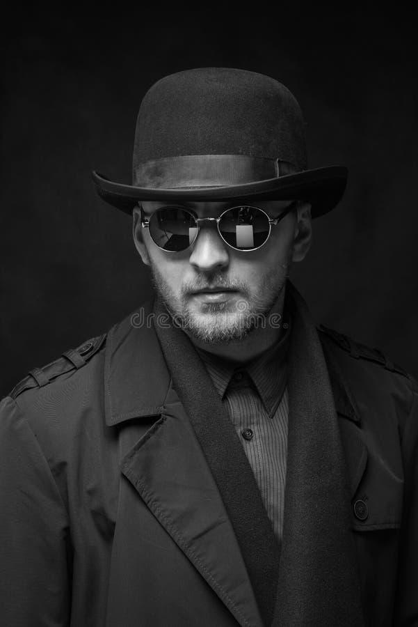 Stående av en man med ett skägg i en hatt och exponeringsglas, en svartvit ram royaltyfri bild