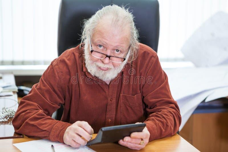 Stående av en man med ett skägg som rymmer en räknemaskin i hans händer arkivbilder