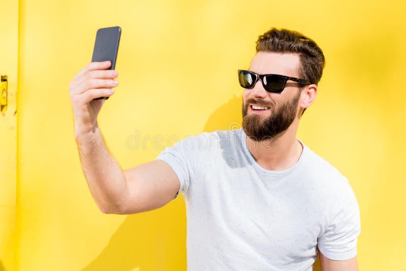 Stående av en man på gul bakgrund royaltyfri fotografi