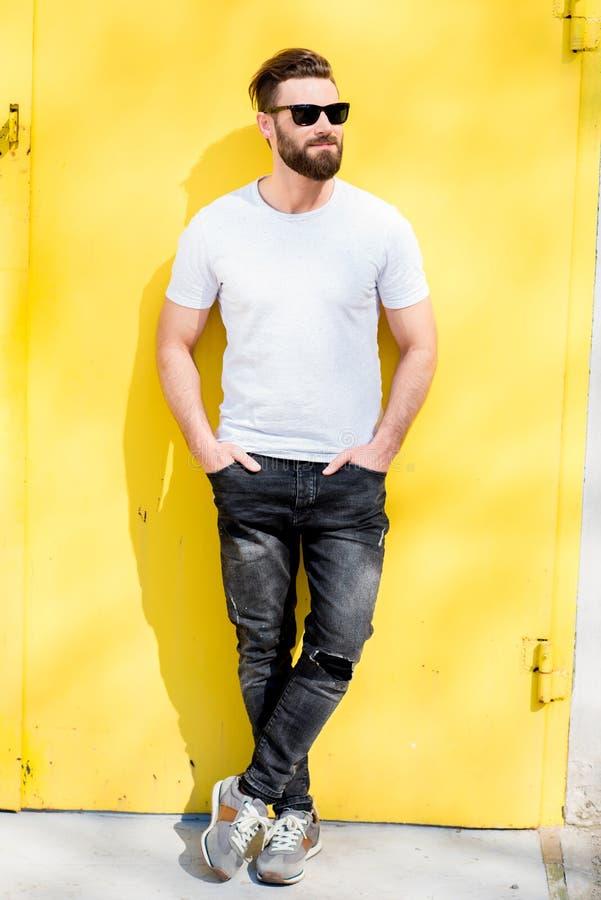 Stående av en man på gul bakgrund arkivfoton