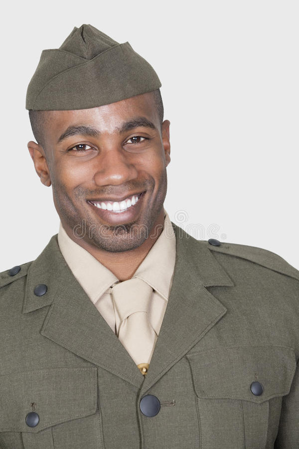 Stående av en manlig afrikansk amerikanUSA-soldat som ler över grå bakgrund royaltyfri fotografi