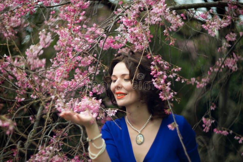 Stående av en medelålders brunett i en blå klänning bredvid en körsbärsröd blomning royaltyfria foton