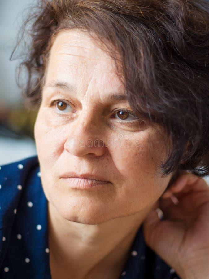 Stående av en medelålders kvinna med ett ledset uttryck för framsidor arkivfoto