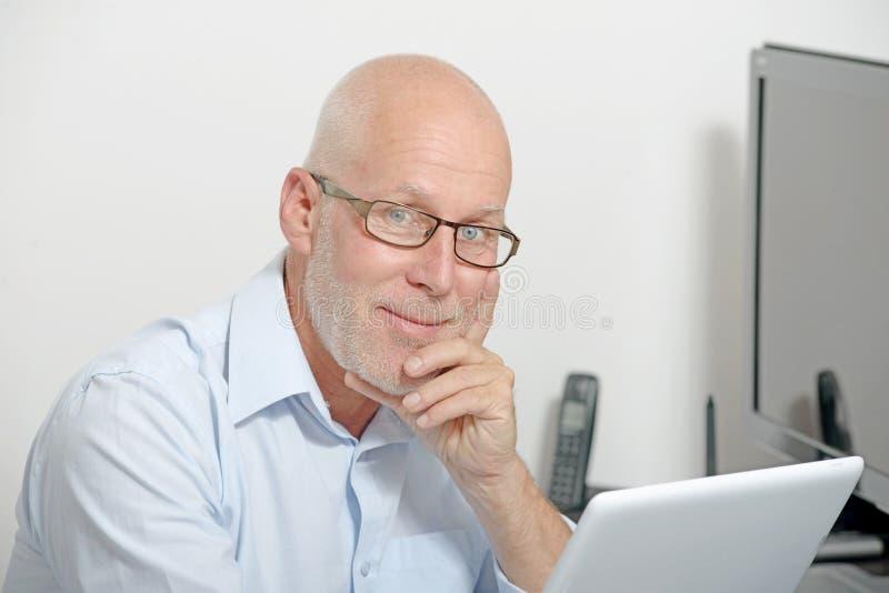 Stående av en medelålders man med en digital minnestavla arkivfoton