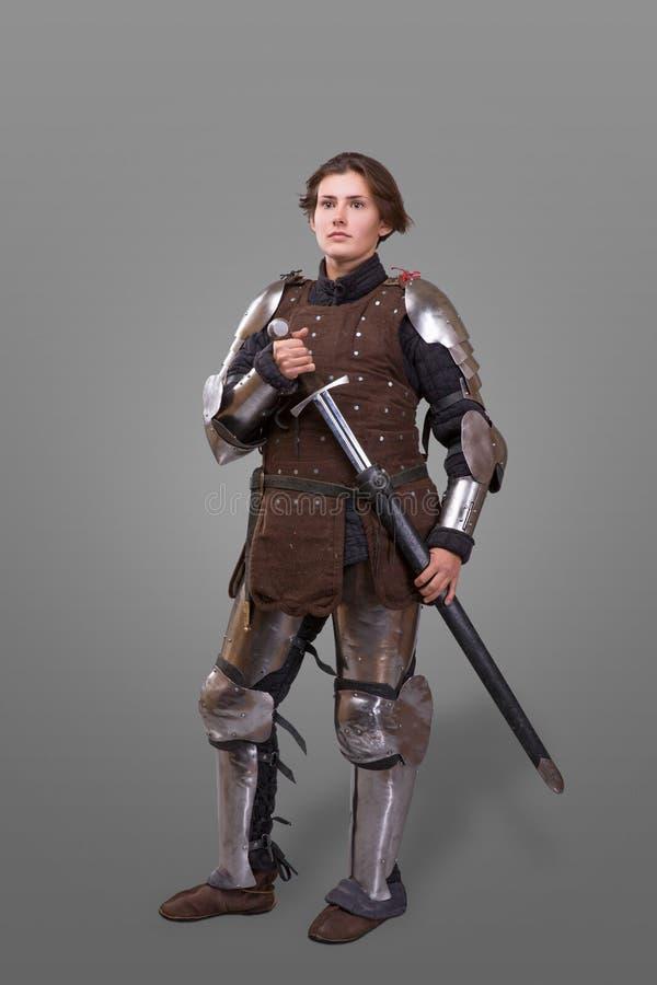 Stående av en medeltida kvinnlig riddare i pansar över grå bakgrund royaltyfria bilder
