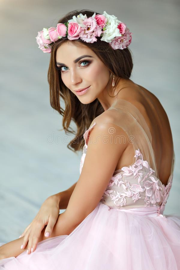 Stående av en mjuk härlig flicka i en rosa klänning och en krans fotografering för bildbyråer