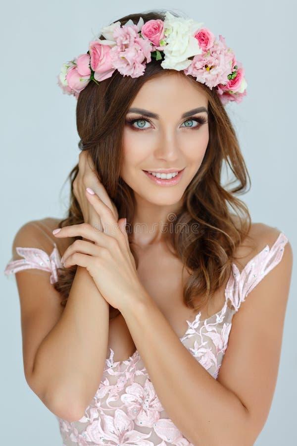 Stående av en mjuk härlig flicka i en rosa klänning och en krans royaltyfri foto