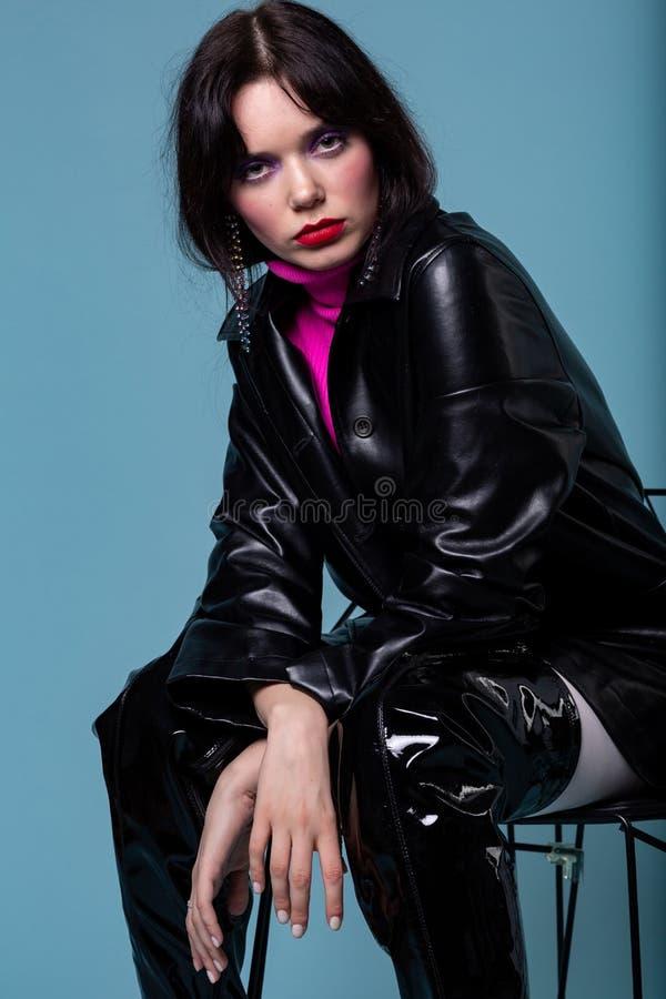 Stående av en modekvinnlig som sitter på stol som poserar i attraktivt moderiktigt planlagt svartläderomslag royaltyfria bilder
