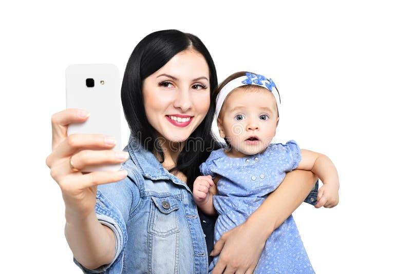 Stående av en moder och hennes dotter som gör selfie på telefonen arkivfoton