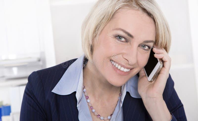 Stående av en mogen eller hög affärskvinna som flörtar på mobil royaltyfri fotografi