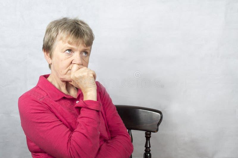 Stående av en mogen kvinna med ett bekymrat ansiktsuttryck fotografering för bildbyråer