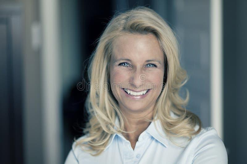 Stående av en mogen kvinna som ler på kameran arkivfoton