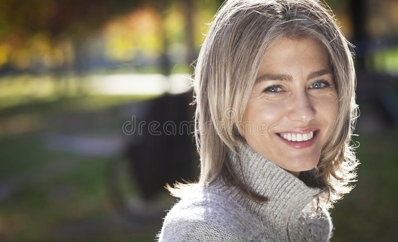 Stående av en mogen kvinna som ler på kameran Grå färghår royaltyfria bilder