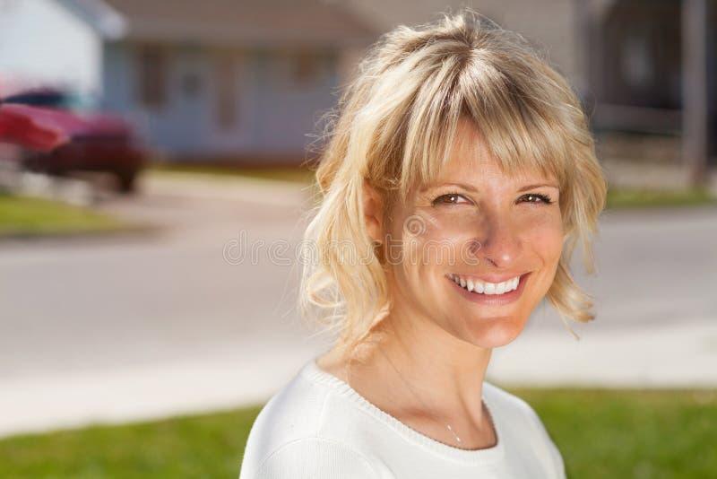 Stående av en mogen kvinna som ler på kameran utanför främst av hennes hus arkivfoto