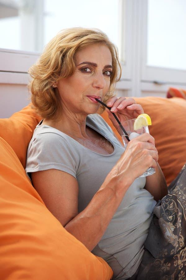 Stående av en mogen kvinna som utomhus kopplar av med en drink royaltyfria bilder