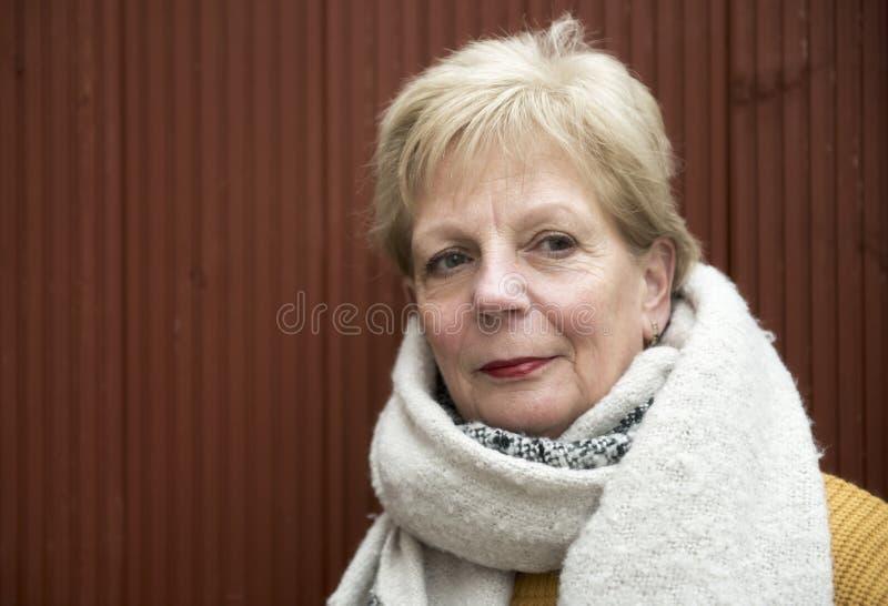 Stående av en mogen kvinna utomhus i vinter med en stor halsduk arkivfoton