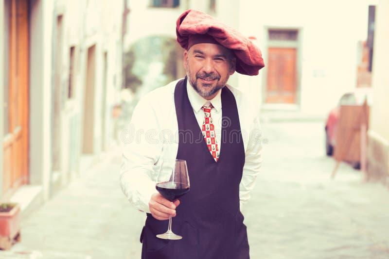 Stående av en mogen lycklig man med exponeringsglas av rött vin utomhus i gammal italiensk by royaltyfria bilder