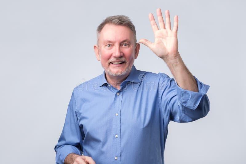 Stående av en mogen man i blå välkomnande för skjortavåghand arkivbild