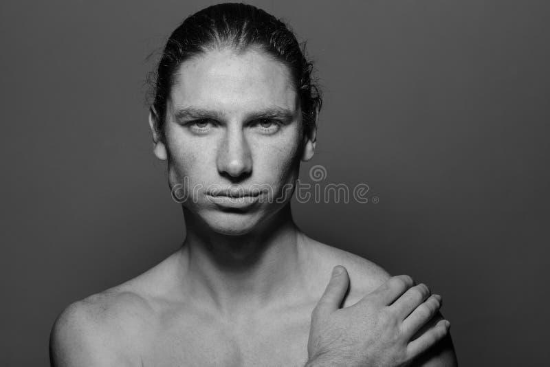 Stående av en muskulös långhårig man med utdraget hår och fräknar som är topless arkivfoton