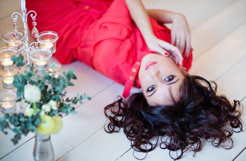 Stående av en mycket härlig flicka i en röd klänning på golvet royaltyfri foto
