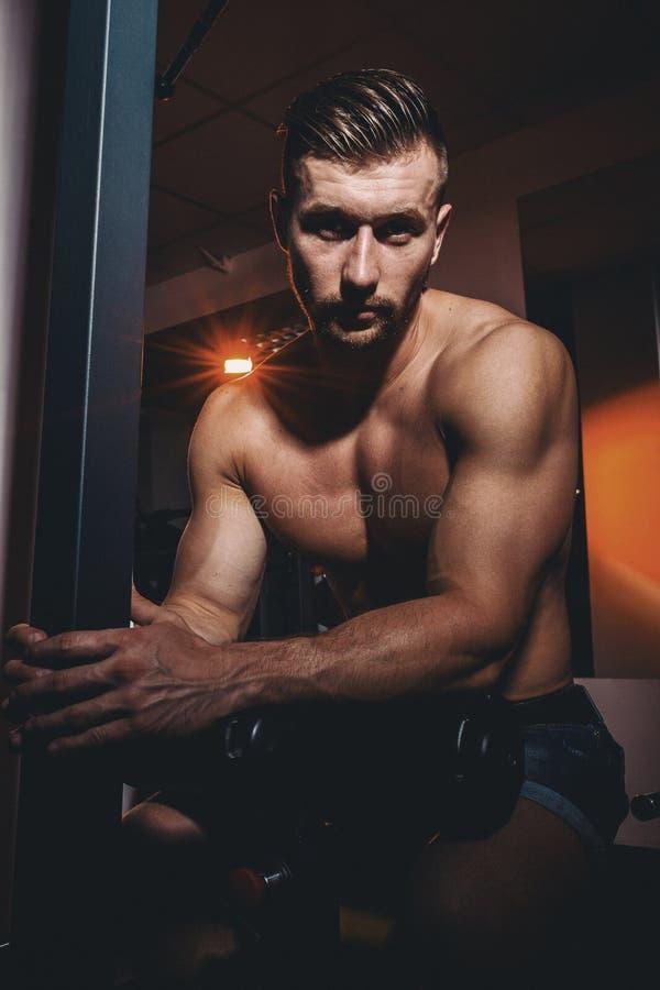 Stående av en mycket muskulös shirtless manlig modell Stilig idrotts- man med stora muskler som poserar på kameran i idrottshalle royaltyfria foton