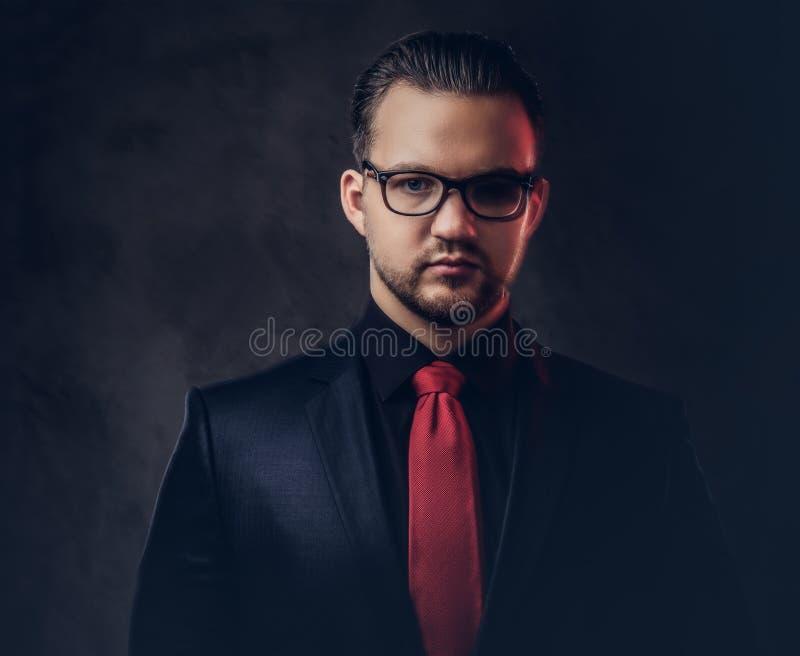 Stående av en mystisk stilfull man i en svart dräkt och ett rött band Isolerat på en mörk bakgrund arkivfoto