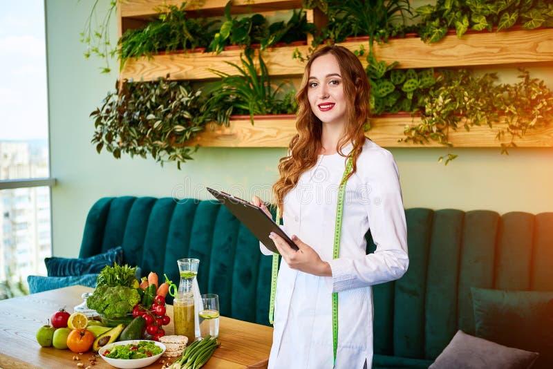 Stående av en näringsfysiolog för ung kvinna i medicinskt kappaanseende med skrivplattan och måttband i kontoret med sund mat på royaltyfri bild