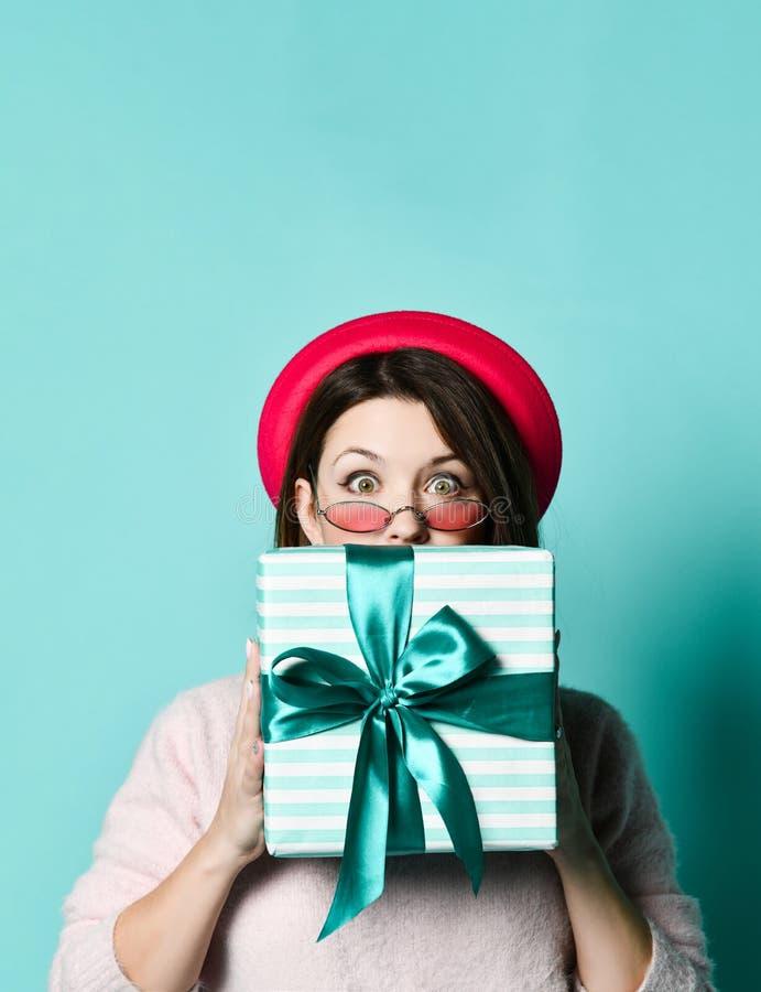Stående av en nätt förvånad flicka i ask för gåva för innehav för lock för filthatt och att dölja bak honom som ser upp arkivfoton