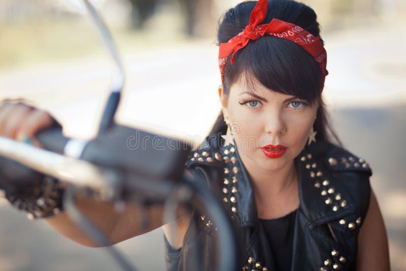 Stående av en nätt flickacyklist eller en gullig kvinna med bärande jeans för stilfullt långt hår som sitter på golv på motorcyke royaltyfri bild