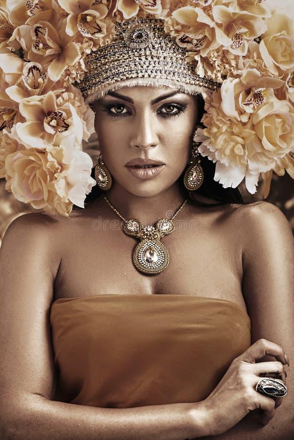 Stående av en nätt kvinna som bär en blommahatt royaltyfri fotografi