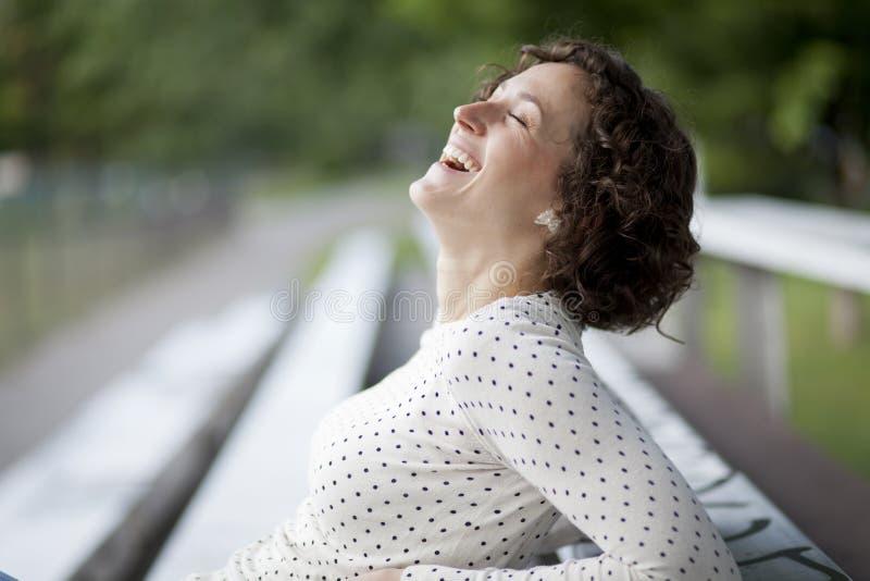 Stående av en nätt kvinna som skrattar på parkera royaltyfri bild
