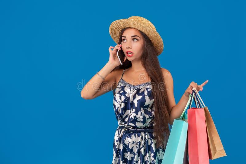 Stående av en nätt kvinna som talar på mobiltelefonen medan hållande shoppingpåsar och bort ser på kopieringsutrymme över blått arkivbilder