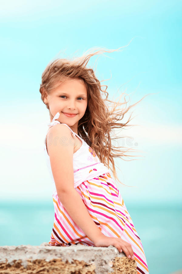 Stående av en nätt liten flicka med att vinka i de långa mumlen för vind royaltyfria foton