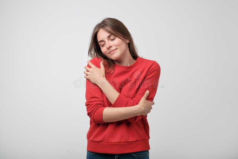 Stående av en nätt ung flicka i röd skjorta som kramar sig arkivfoto