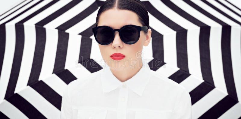 Stående av en nätt ung kvinna i den vit chemisen och solglasögon med ljusa målade kanter fotografering för bildbyråer