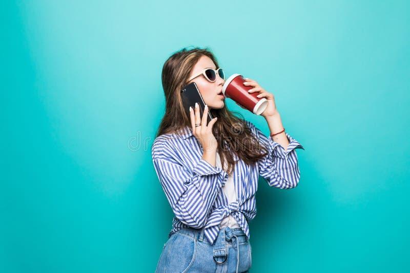 Stående av en nätt ung kvinna i tröja genom att använda mobiltelefonen, medan rymma den takeaway kaffekoppen isolerad över blå ba arkivfoto
