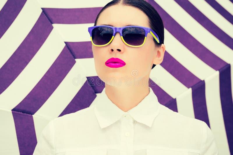 Stående av en nätt ung kvinna med färgrik solglasögon royaltyfria foton