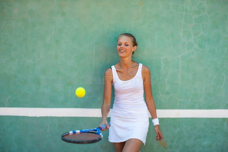 Stående av en nätt, ung kvinnlig tennisspelare framme av en utbildande vägg fotografering för bildbyråer