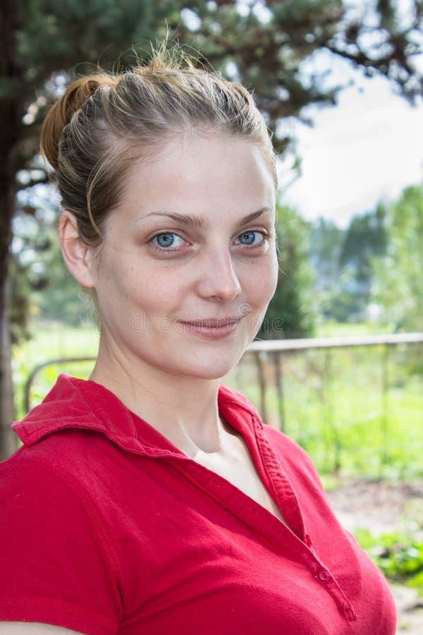 Stående av en naturlig ung kvinna som utomhus ler på kameran fotografering för bildbyråer