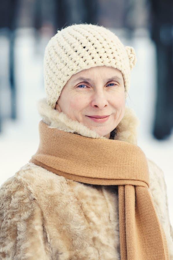 Stående av en naturlig vuxen kvinna med en halsduk och woolen mummel royaltyfri foto