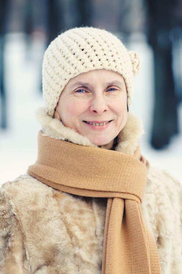 Stående av en naturlig vuxen kvinna med en halsduk och woolen mummel arkivfoto