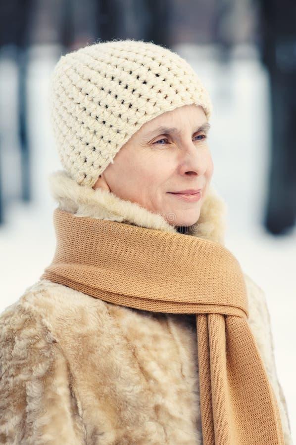 Stående av en naturlig vuxen kvinna med en halsduk och woolen mummel arkivbilder