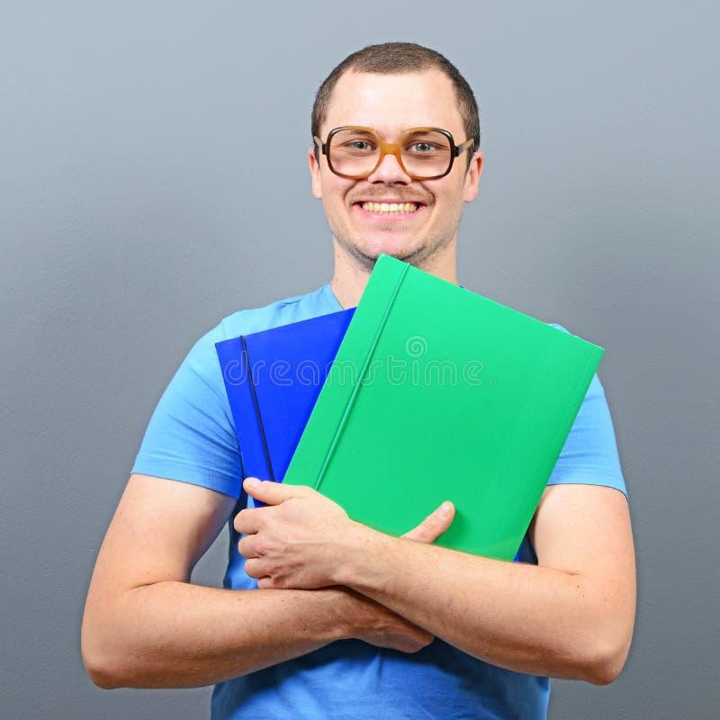 Stående av en nerd som rymmer böcker med retro exponeringsglas arkivfoton