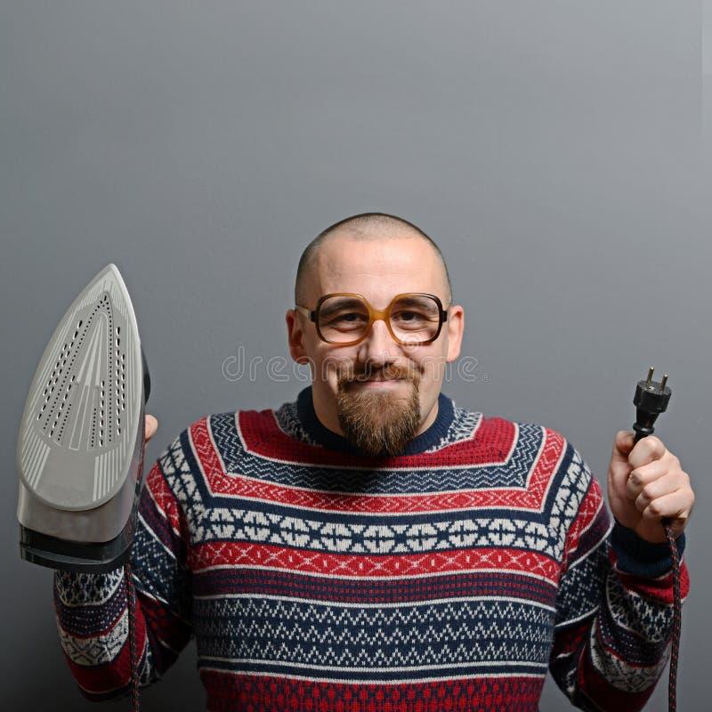 Stående av en nerdy man som rymmer järn mot grå bakgrund royaltyfri bild