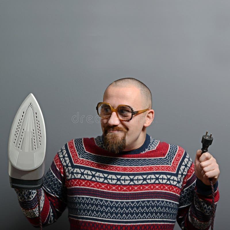 Stående av en nerdy man som rymmer järn mot grå bakgrund royaltyfri foto