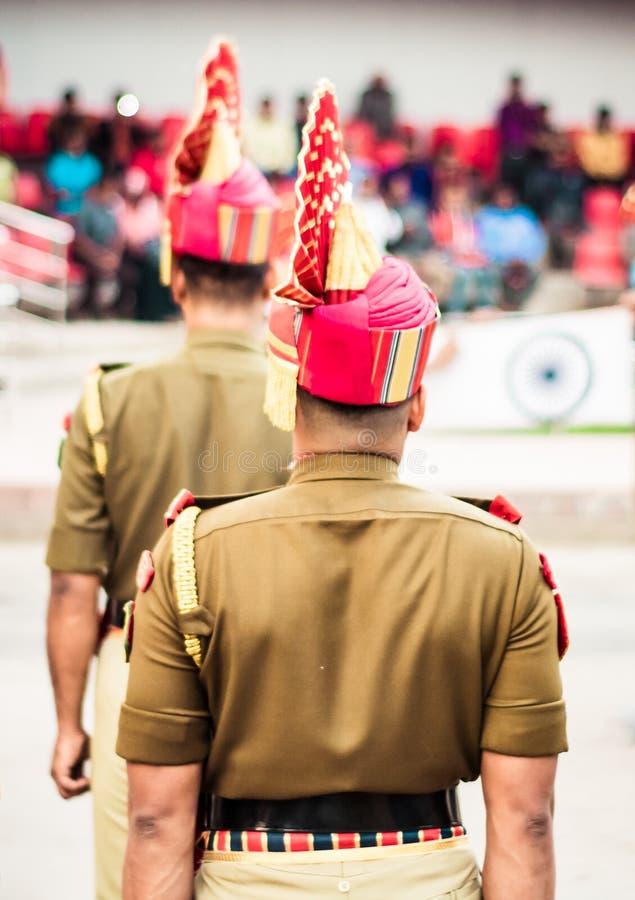 Stående av en oigenkännlig indisk polis som i rad står isolated rear view white arkivfoto