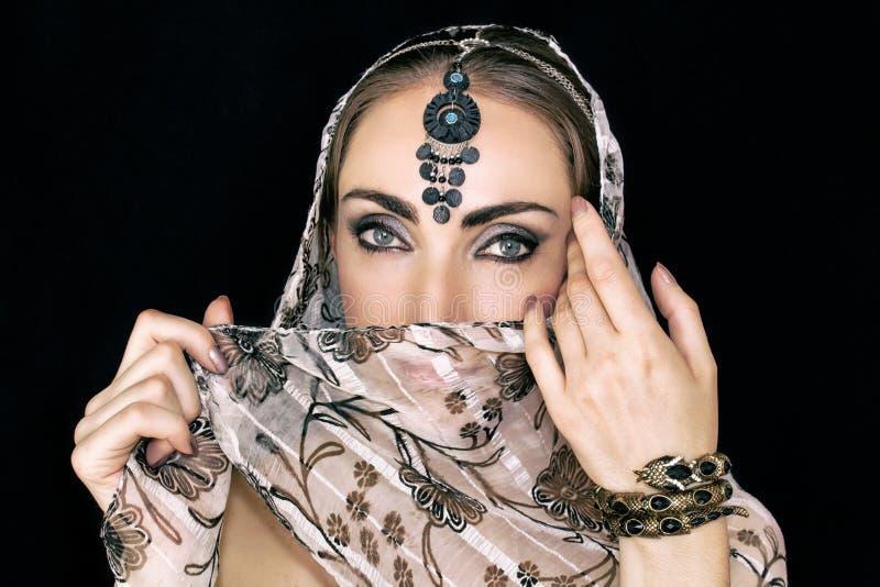 Stående av en orientalisk ung kvinna i en halsduk med en prydnad och juvlar på en svart bakgrund royaltyfria bilder